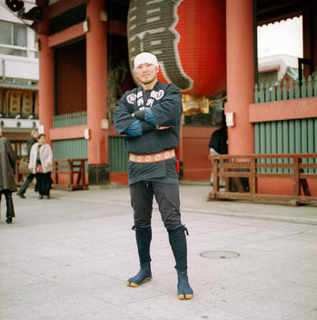 Man Standing In Front Of Temple In Traditional Clothing, Asakusa, Tokyo, Japan