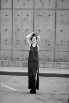 Black and white urban street fashion shoot with a beautiful young woman and model Kate Tiskevics standing in a long black dress posing in front of a concrete wall in downtown on a summer day. Denver, Colorado