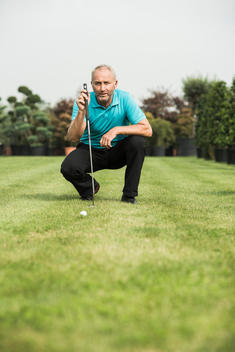 Golf player crouching on turf looking at golf ball