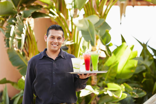 Hispanic server carrying tray of drinks outdoors