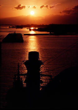The red sun rises in the distance over water and silhouettes a shipping dock.
