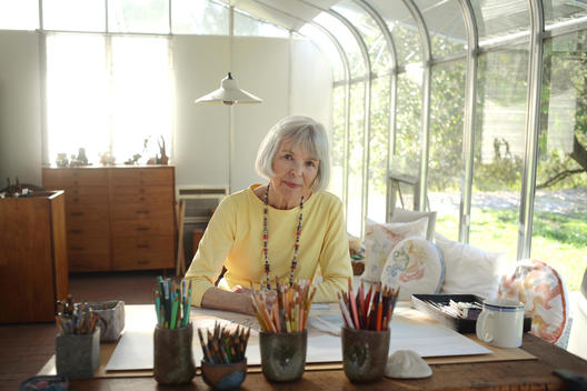 A healthy creative attractive active senior woman enjoys retirement while painting and drawing in her sun-filled artist studio.