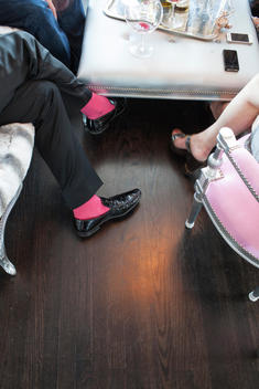 overhead view of a man\'s feet with red socks and woman\'s feet with high heels at a dinner party in a living room with a upholstered coffee table with iPhone cell phones on it.