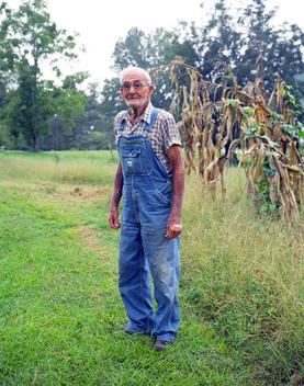 An Old Man Wearing Overalls Standing Next To A Corn Field.