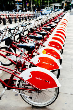 A row of bicycles sit waiting to be rented in Barcelona, Spain.
