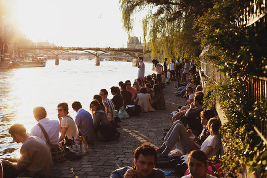 A group of young people sitting along the Seine river at sunset in Paris.