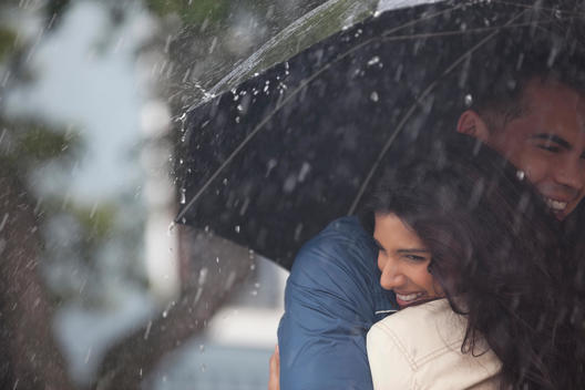 Happy couple hugging under umbrella in rain