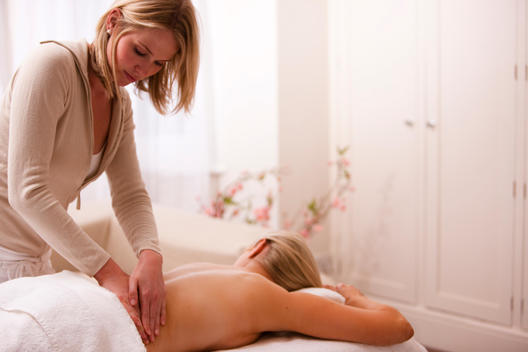Masseuse giving a woman a back massage