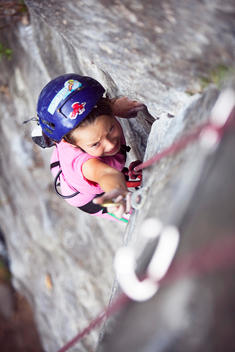 A young girl looks up with deep concentration as she attempts to clip a bolt on a sport climbing route in Santa Clara, Ecuador.
