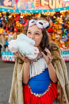 girl eating cotton candy at carnival