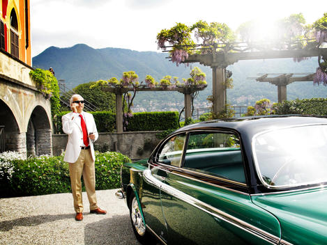 A Man In The Car Park Of A Grand Country Estate, With A Photographer In The Distance.
