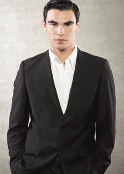Fashion Portrait Of A Young European Male Model Wearing A Black Suit And A White Shirt, Standing Infront Of A Concrete Wall, He Has Brown Eyes And Dark Brown Short Hair