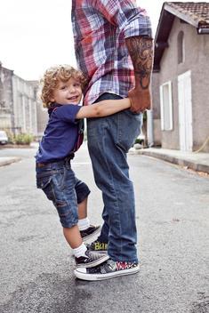 little boy standing on father feet