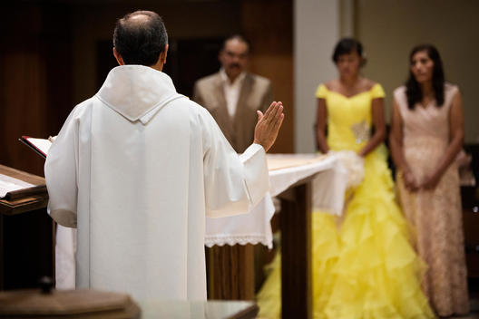 Hispanic family celebrating quinceanera with priest in Catholic church