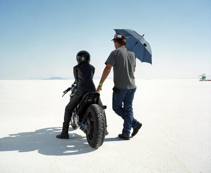 A Motorcycle Rider On A Motorcycle And A Man With An Umbrella On The Salt Flats.