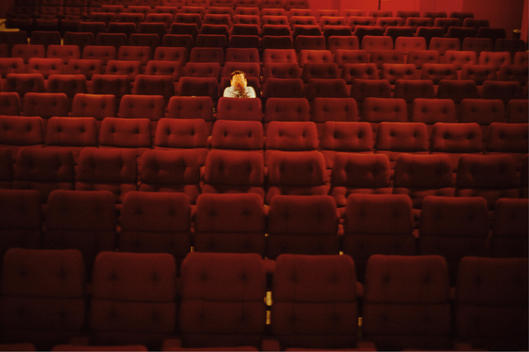 Man Sitting Alone In Movie Theater, Covering His Eyes Because He\'S Scared