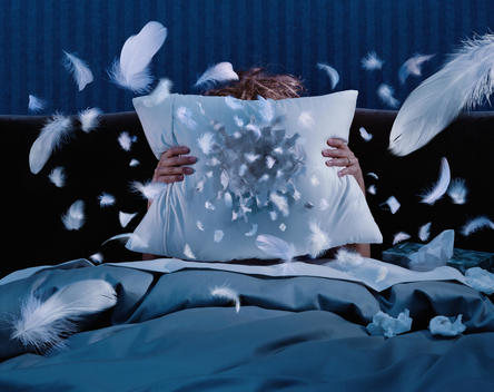 Woman In Bed Sneezing Into A Pillow Creating A Hole And Flying Feathers.