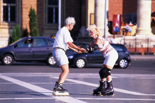 Senior couple holding hands as they rollerblade on a street in Budapest, Hungary.