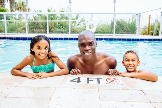 Father and children smiling in swimming pool