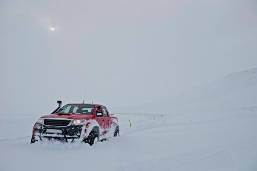 Mature woman driving red pick up truck on deep snow road, Fljotsheidi, North Iceland