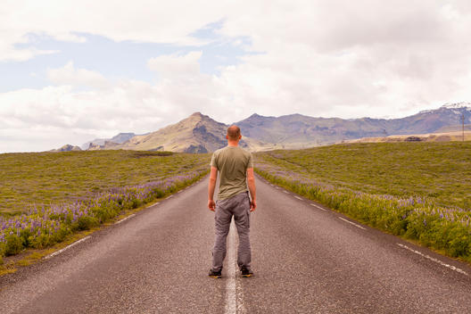 Man facing away from viewer looking down the centre of a mountain road, mountain range is visible in the distance.