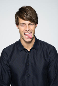 guy in navy button down shirt sticking tongue out