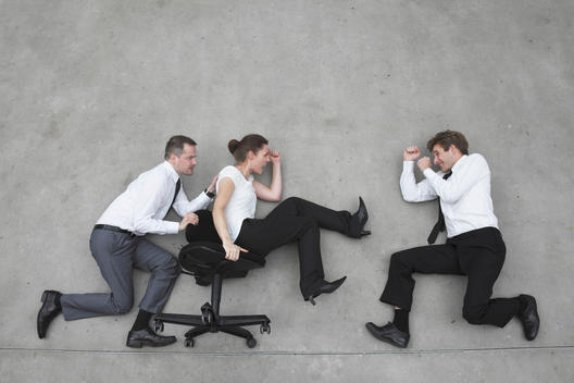 Three business people, business man pushing businesswoman in office chair, side view, elevated view