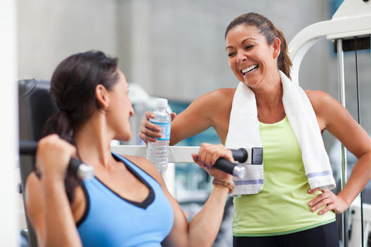 Woman exercising in health club with friend