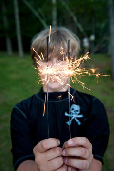 a boy celebrates july 4th with sparklers