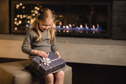 Non-specific holiday portrait of a young girl wth a gift on her lap, seated in front of a modern lit fireplace in which holiday lights are reflected on the glass.