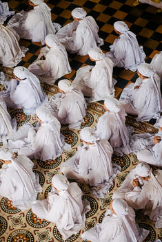 Followers of the Cao Dai religion pray in the Great Temple of Cao Dai. Tay Nihn, Vietnam