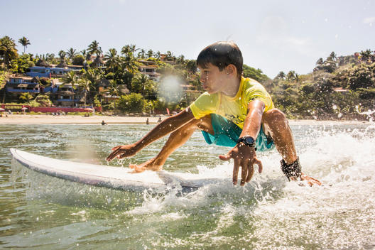 Mixed race boy surfing in ocean