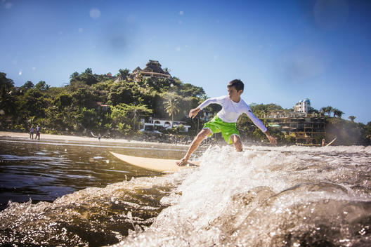 Mixed race boy surfing in ocean