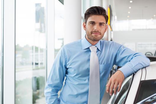At the car dealer, Man leaning at new car