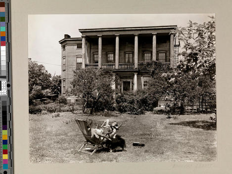 Two people relax in deck chairs across the road from a grand, multi-storied house.