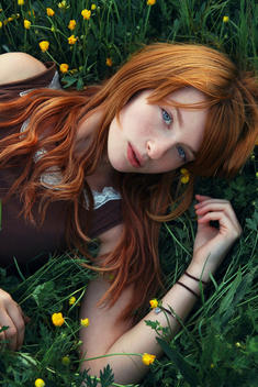 A young woman with red hair lying in the grass filled with yellow flowers