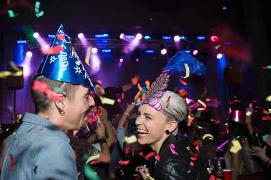 Confetti falling around couple enjoying New Year celebration