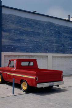 Vintage Pickup Truck Parked Next To Painting Of Ocean On Wall