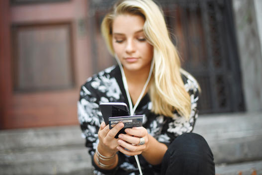 Girl with ear buds on listening to music while on her sumsung phone and hodling her credit card