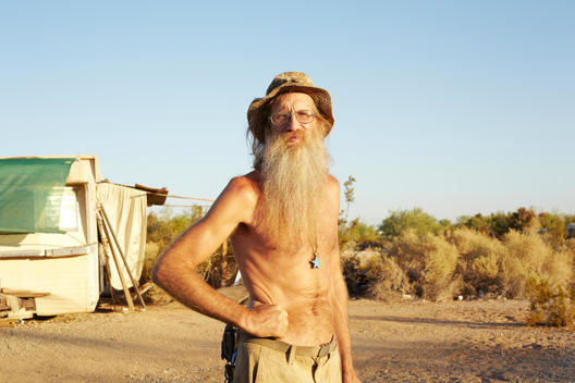 Mature Hippie Man With Long Beard Outside Of Trailer In Slab City, Ca