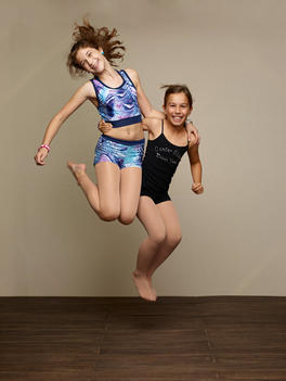 Two young female dancers jumping.