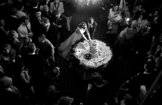 A Newly Married Couple Cut The Wedding Cake At Their Reception
