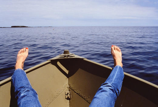 Woman\'s feet and legs over the bow of small boat