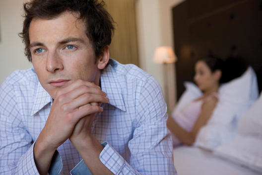 Man sitting on edge of bed looking off contemplatively with woman in bed in background.