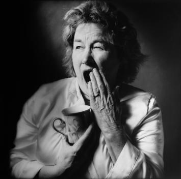 Senior Woman, Caucasian Appearance, Yawning, Holding Coffee Mug.