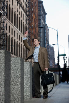 A Business Man Hails A Cab On A Chicago Street.