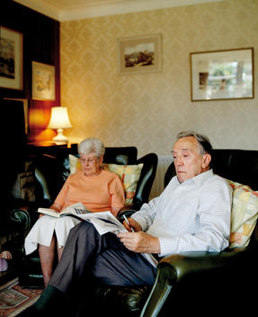 Senior Couple Reading In Their Living Room.
