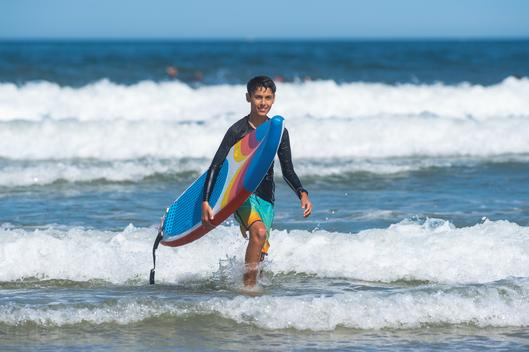 A young man walking out of the ocean with his surfboard after surfing in the ocean on a sunny day in San Diego, California