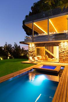 Modern house overlooking illuminated swimming pool at night