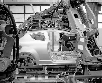 Car part being welded by automated robots on an assembly line.